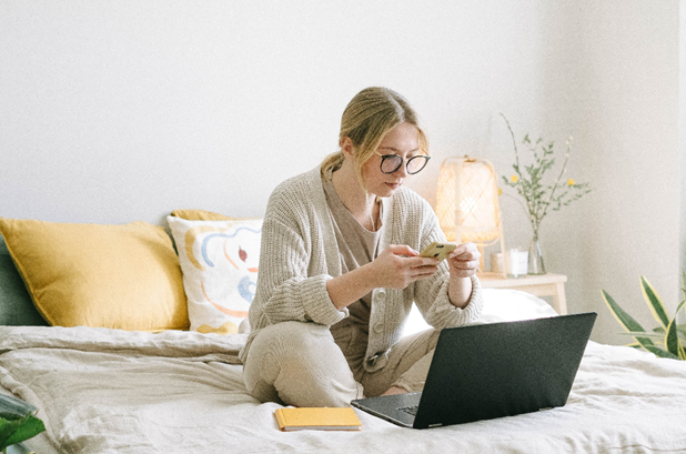 Women with glasses sitting on bed working Customer support jobs