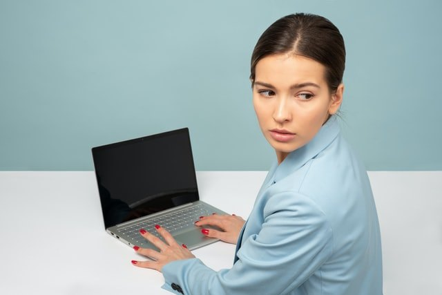 Woman in blue suit is looking behind her back while working online